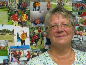 Photo by Sally Smith: Heather - Heather Murphy stands in front of one of many photo boards where volunteers post pictures of search and rescue exercises and searches.